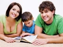 Libro de lectura preescolar del muchacho con sus padres Imágenes de archivo libres de regalías