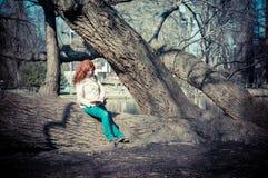Libro de lectura principal rojo hermoso de la mujer joven Imagen de archivo