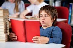 Libro de lectura relajado del muchacho en la tabla en biblioteca Fotos de archivo