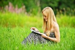 Libro de lectura rubio joven de la mujer Fotos de archivo libres de regalías