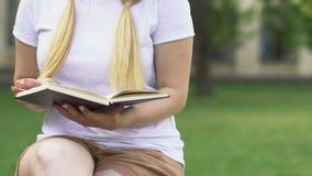 Libro de lectura rubio de la muchacha al aire libre, estudiante que se prepara para el examen, revisando la información almacen de video