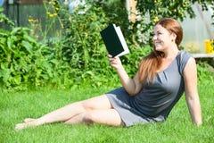 Libro de lectura sonriente atractivo de la mujer Fotografía de archivo libre de regalías