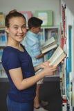 Libro de lectura sonriente de la colegiala en biblioteca en la escuela Imágenes de archivo libres de regalías