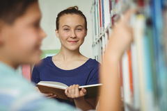 Libro de lectura sonriente de la colegiala en biblioteca en la escuela Imagen de archivo libre de regalías