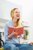 Libro de lectura sonriente de la muchacha del adolescente en cocina Fotografía de archivo
