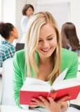 Libro de lectura sonriente de la muchacha del estudiante en la escuela Imágenes de archivo libres de regalías
