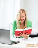 Libro de lectura sonriente de la muchacha del estudiante en universidad Imagenes de archivo