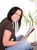 Libro de lectura sonriente de la mujer Fotos de archivo