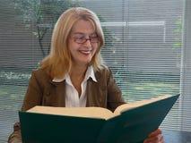 Libro de lectura sonriente de la mujer Imagen de archivo