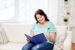 Libro de lectura sonriente de la mujer del tamaño extra grande en casa Foto de archivo libre de regalías