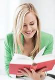 Libro de lectura sonriente de la mujer joven en la escuela Fotos de archivo libres de regalías