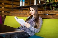 Libro de lectura sonriente de la mujer joven en lugar del café o de trabajo Imagen de archivo