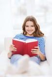 Libro de lectura sonriente del adolescente en el sofá Imagenes de archivo