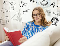Libro de lectura sonriente del adolescente en el sofá Imágenes de archivo libres de regalías
