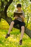 Libro de lectura sonriente del muchacho en la naturaleza Imagen de archivo