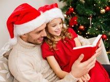 Libro de lectura sonriente del padre y de la hija Imágenes de archivo libres de regalías