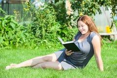 Libro de lectura sonriente feliz de la muchacha, sentada en hierba verde Fotos de archivo libres de regalías