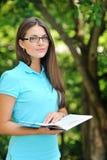 Libro de lectura sonriente hermoso de la mujer joven, contra verde del verano Imagenes de archivo