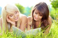 Libro de lectura sonriente hermoso joven de dos mujeres fotografía de archivo libre de regalías