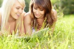 Libro de lectura sonriente hermoso joven de dos mujeres imagen de archivo