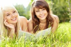 Libro de lectura sonriente hermoso joven de dos mujeres imagen de archivo libre de regalías