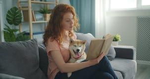 Libro de lectura sonriente de la muchacha en casa que se sienta en el sofá y acariciar el perrito lindo almacen de metraje de vídeo