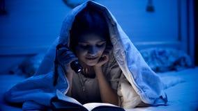 Libro de lectura sonriente de la niña en dormitorio oscuro antes de ir a dormir Imagenes de archivo