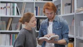 Libro de lectura sonriente positivo de los estudiantes y discusión en biblioteca metrajes