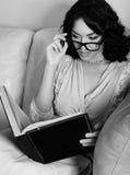 Libro de lectura trigueno joven atractivo de la mujer imagen de archivo