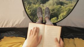 Libro de lectura turístico del hombre joven en tienda en el camping en bosque