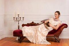 Libro de lectura victoriano de la mujer en el sofá de desfallecimiento foto de archivo libre de regalías