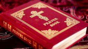 Libro de oración con la cruz ortodoxa en la tabla con luz de una vela que oscila suave almacen de metraje de vídeo
