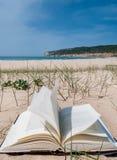 Libro de texto abierto en la playa blanca de la arena Imagenes de archivo