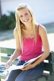 Libro de texto femenino de la lectura de Sitting On Bench del estudiante universitario Fotografía de archivo libre de regalías