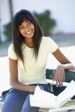 Libro de texto femenino de la lectura de Sitting On Bench del estudiante universitario Fotografía de archivo