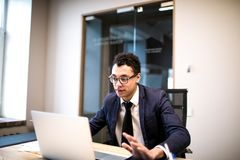 Libro de texto orgulloso masculino de la tenencia del CEO durante trabajo sobre netbook portátil imagenes de archivo