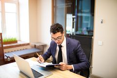 Libro de texto orgulloso masculino de la tenencia del CEO durante trabajo sobre netbook portátil imagen de archivo libre de regalías