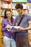 Libro de texto sonriente de la lectura del estudiante de los amigos Imagen de archivo libre de regalías