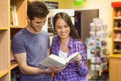 Libro de texto sonriente de la lectura del estudiante de los amigos Imágenes de archivo libres de regalías