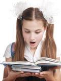 Libro de texto sorprendido de la lectura de la colegiala. Foto de archivo