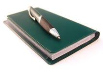 Libro de verificación con la pluma Foto de archivo libre de regalías