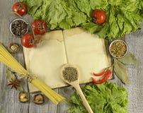 Libro del cocinero con espaguetis y especias Fotos de archivo