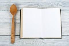 Libro del espacio en blanco del cocinero de la receta en el fondo de madera, cuchara, rodillo, mantel a cuadros Fotografía de archivo