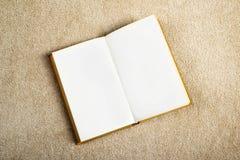 Libro del vintage con las páginas en blanco en la moqueta foto de archivo