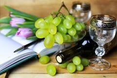 Libro della bottiglia di vino ed uva di vetro Immagine Stock
