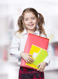 Libro della cartella della tenuta del supporto dell'allievo della ragazza del bambino in camicia bianca Fotografie Stock