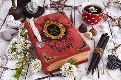 Libro della strega con le candele nere, tazza di tè e decorazioni mistiche Fotografia Stock Libera da Diritti