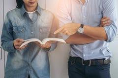 Libro della tenuta del giovane studente allegro e lettura diritti, classm Fotografia Stock
