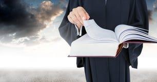 Libro della tenuta del giudice davanti alle nuvole del cielo Fotografie Stock