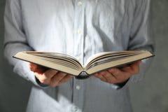 Libro della tenuta dell'uomo in mani immagine stock